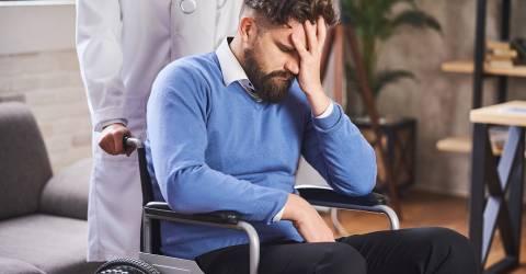 Trieste man in een rolstoel die een hand voor zijn gezicht houdt en geduwd wordt door een arts