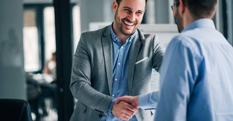 Vrolijke jonge manager geeft een handdruk aan nieuwe medewerker