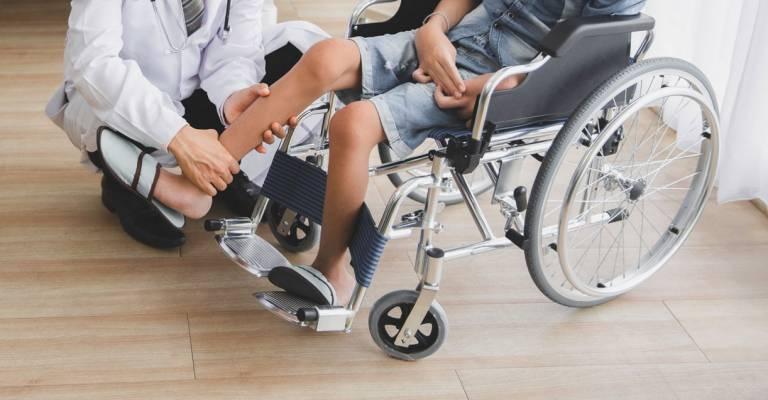 Arts die been van patiënt in rolstoel in het ziekenhuis controleert